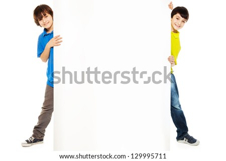 Two handsome boys showing blank white board for advertising to be inserted - stock photo