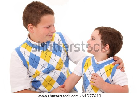 Two handsome brothers smiling at each other over white. Dressed alike. Age 10 and 3. - stock photo