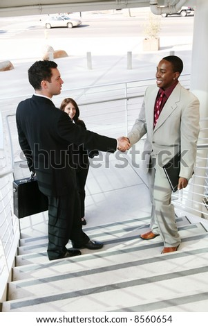 Two handsome business men shaking hands to confirm a deal - stock photo