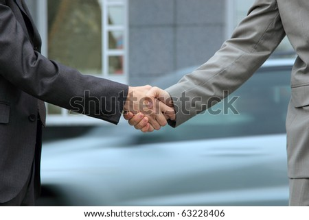 two Handsome  Businessman shaking hands in front of corporate - stock photo