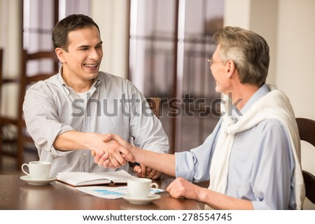 Two handsome businessmen in shirts sitting at the wooden table in urban cafe and shaking hands. - stock photo
