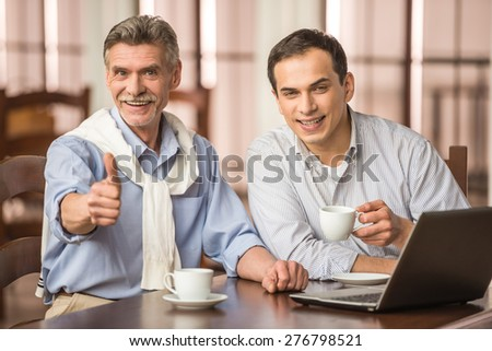 Two handsome businessmen in shirts sitting at the wooden table in urban cafe and using laptop. - stock photo