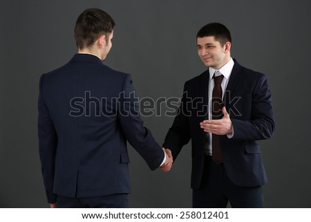 Two handsome businessmen on gray background - stock photo