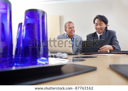 Two handsome businessmen working together on a laptop and digital tablet - stock photo