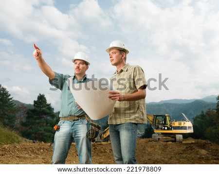 two handsome caucasian engineers comparing blueprint with actual construction - stock photo