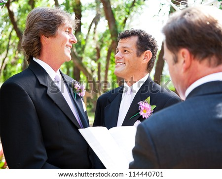 Two handsome gay grooms getting married  in beautiful park-like setting. - stock photo