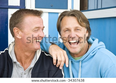 Two handsome laughing gay men.