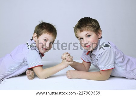 two handsome little boys prepare for armwrestling battle - stock photo