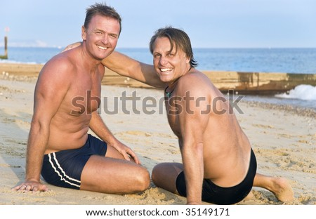 Two handsome mature gay men having fun on beach. - stock photo