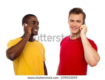 Two handsome men communicating on cellphone. African guy looking at caucasian male.
