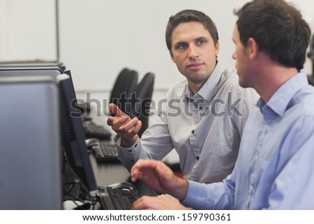 Two handsome men talking while sitting in computer class pointing at monitor - stock photo