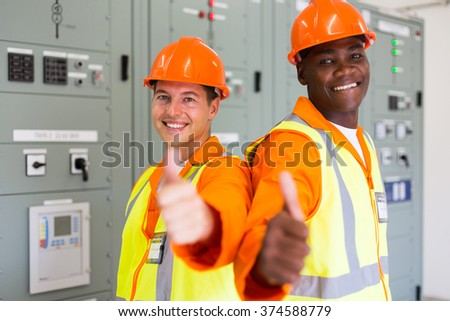 two handsome power company technical co-workers with thumbs up  - stock photo