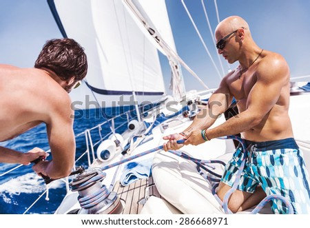 Two handsome shirtless sailors working on sailboat, pulling rope on crank, summer time activity, spending vacation in a sea traveling - stock photo
