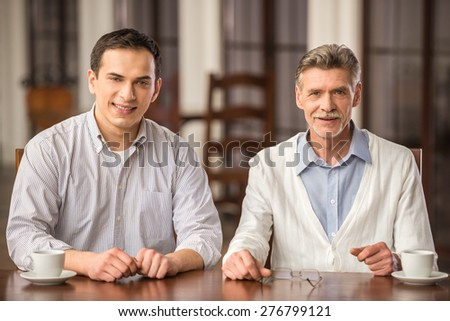 Two handsome smiling businessmen in shirts sitting at the wooden table in urban cafe. - stock photo