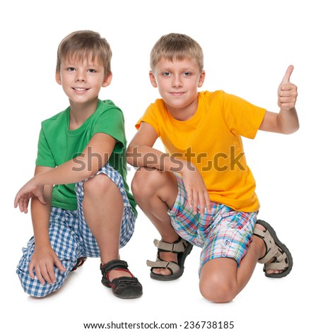 Two handsome young boys are sitting together on the white background - stock photo