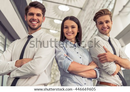 Two handsome young businessmen and lady in classic clothes are looking at camera and smiling, standing with crossed arms near the office building - stock photo