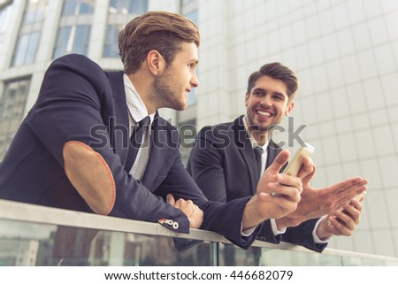 Two handsome young businessmen are talking and smiling, leaning on balcony balustrade outside the office building. One guy is holding a phone - stock photo