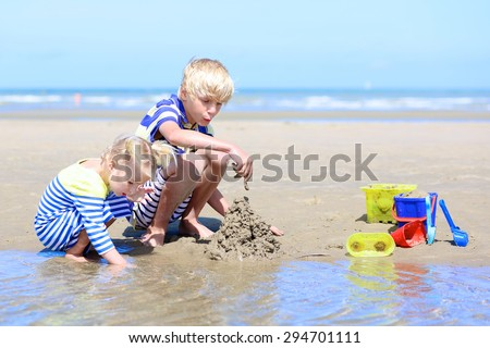 Two happy active children, teenage boy with his little sister, cute blonde toddler girl, playing with plastic toys building sand castles sitting on wide sandy North European beach