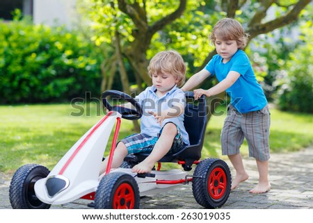 Two happy active little kid and sibling boys having fun with toy race car in summer garden, outdoors. Adorable brother pushing the car with younger child. Outdoor games for children in summer concept. - stock photo