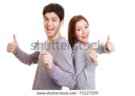 Two happy adolescent teens with European driving license holding thumbs up - stock photo