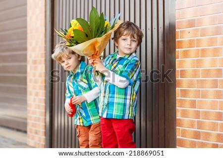 Two happy adorable little sibling boys with blooming  flowers, outdoor. For mother's day or birthday congratulation. - stock photo