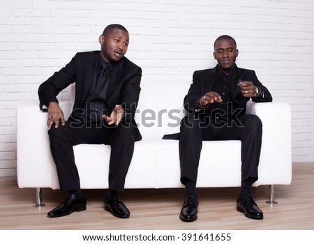 two happy african man businessmen in black suit on white sofa