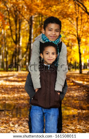 Two happy 8 and 10 boys black brothers standing in the autumn orange park