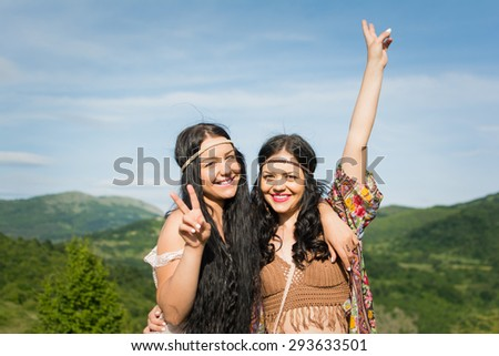Two happy and free young hippie women smiling gesturing peace sign standing in nature on sunny summer day. No retouch, natural light. - stock photo
