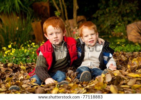 Two happy and smiling brothers or sons are sitting and hugging in a pile of colorful yellow and brown autumn / fall leaves in a garden or park setting - stock photo