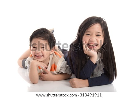 Two  happy asian children lying and leaning on each other ,white background isolated - stock photo