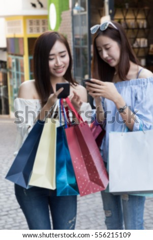 two happy asian shopaholic women with smartphone and colorful shopping bags at department store shopping mall, blur background