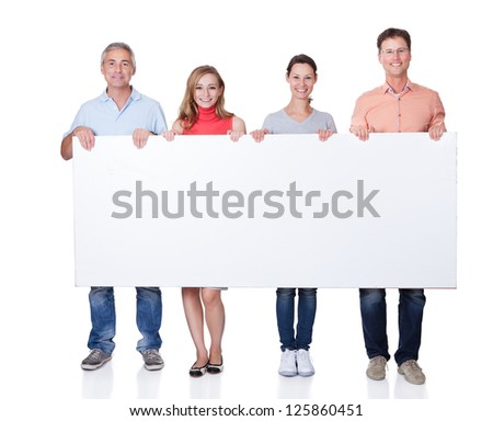 Two happy attractive middle-aged couples in casual clothing holding up a blank horizontal board or banner isolated on white - stock photo