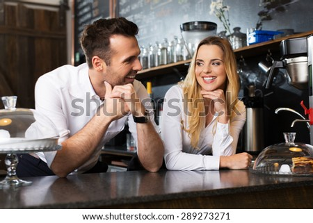 Two happy  bartenders talking behing the bar - stock photo