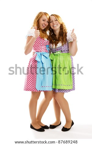 two happy bavarian dressed girls showing thumbs up on white background - stock photo