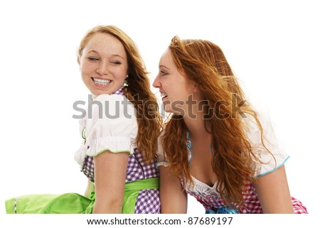 two happy bavarian dressed women looking at each other on white background - stock photo