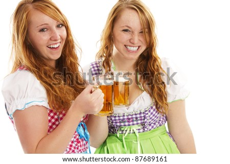 two happy bavarian girls with beer on white background - stock photo