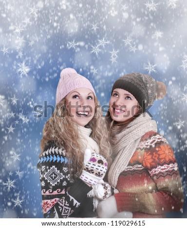 Two happy beautiful girls enjoy for snowfall - stock photo