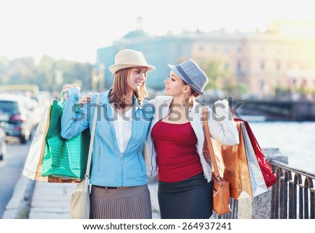Two happy beautiful girls with shopping bags embrace in the city outdoor - stock photo