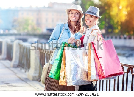 Two happy beautiful girls with shopping bags in the city outdoor - stock photo