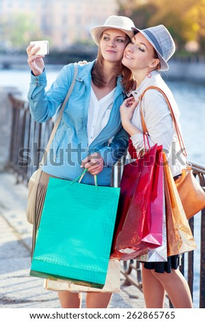 Two happy beautiful girls with shopping bags taken picture of themself in the city  - stock photo