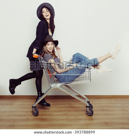 Two happy beautiful teen girls driving shopping cart indoors, lifestyle concept - stock photo