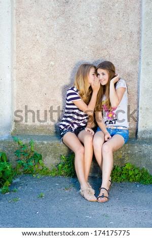Two happy beautiful teenage girls sharing secret on summer day - stock photo