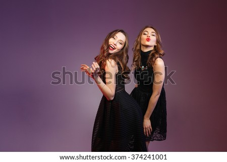 Two happy beautiful young women in black dresses dancing and sending kisses over colorful background - stock photo