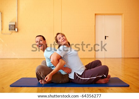 Two happy Best Ager doing back exercises in gym
