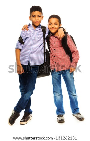 Two happy black brothers standing together with backpack hugging, full height portrait isolated on white - stock photo