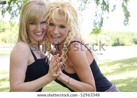 Two Happy Blond Women in the Park Holding each Other - stock photo