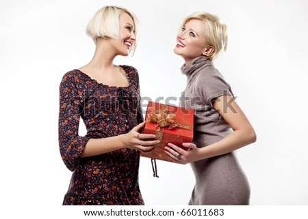 Two happy blond women with a present box - stock photo
