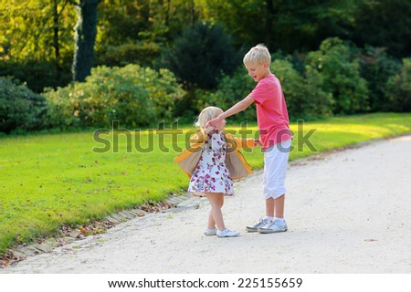 Two happy blonde kids, brother and sister, teenage boy and cute toddler girl wearing yellow jacket and colorful necklace, playing together in the park - stock photo