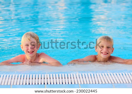 Two happy boys, laughing teenage twin brother, enjoying sunny summer vacation playing in outdoors swimming pool - stock photo