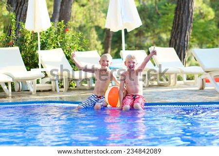 Two happy boys, laughing teenage twin brother, enjoying sunny summer vacations playing with inflatable ball in outdoors swimming pool - stock photo